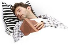 Чтение молодого человека в кровати уснувшей Стоковое фото RF