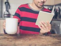 Чтение молодого человека и выпивая кофе Стоковое Фото