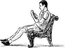 Чтение молодого человека на скамейке в парке Стоковое Фото