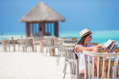 Чтение молодой женщины на кафе пляжа внешнем стоковое изображение rf