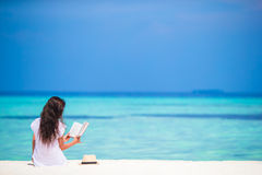 Чтение молодой женщины на тропическом белом пляже стоковые фото