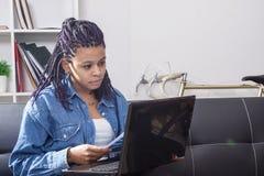 Чтение молодой женщины перед компьютером Стоковое Изображение