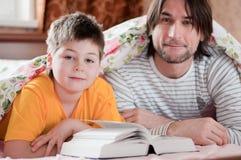 Чтение папаа и сынка в кровати Стоковое фото RF