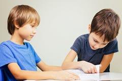 Чтение практики мальчика с его братом дома стоковое фото