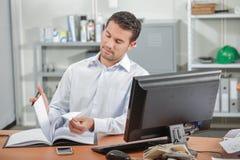 Чтение работника офиса на столе Стоковые Изображения
