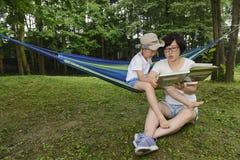 Чтение ребенк с мамой совместно стоковые фотографии rf
