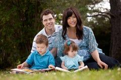 Чтение семьи в парке стоковая фотография