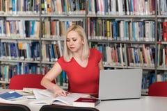Чтение студента от книги в библиотеке Стоковые Изображения RF