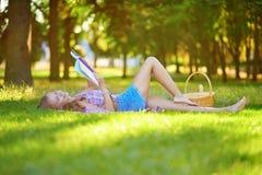 чтение травы девушки лежа Стоковое Фото
