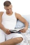 чтение человека книги кровати лежа Стоковое фото RF