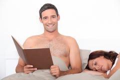 Чтение человека в кровати Стоковое Фото