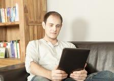 Чтение человека расслабляющее eBook Стоковое Изображение RF
