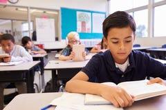 Чтение школьника на его столе в классе начальной школы стоковые фото