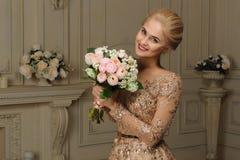 Чувственная блондинка девушки в улыбках бежевого платья нежных в интерьере конец вверх Стоковая Фотография