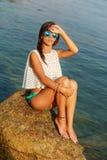 Чувственная девушка на большой каменной близко воде Стоковая Фотография
