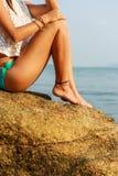 Чувственная девушка на большой каменной близко воде Стоковые Фотографии RF
