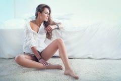 Чувственная женщина брюнет в спальне Стоковые Изображения
