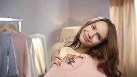 Чувственная женщина выбирая платье Студия одежд милой девушки пробуя дома видеоматериал