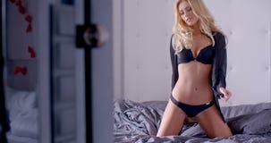 Чувственная женщина в сексуальном нижнем белье вставать на кровати акции видеоматериалы