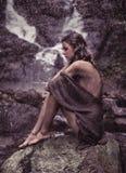 Чувственная женщина отдыхая близко к водопаду стоковая фотография rf