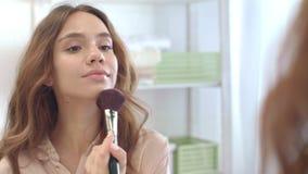 Чувственная женщина прикладывая порошок косметической щеткой пока макияж утра в bathroom сток-видео