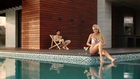 Чувственная женщина прикладывая suncream на ногах около бассейна на роскошном доме сток-видео