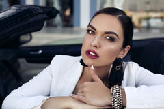 Чувственная женщина при темные волосы представляя в роскошном автомобиле Стоковая Фотография