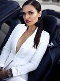 Чувственная женщина при темные волосы представляя в роскошном автомобиле Стоковые Фотографии RF
