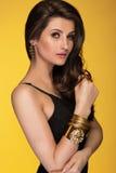 Чувственная красивая женщина брюнет представляя в черных платье и золоте Стоковое Фото