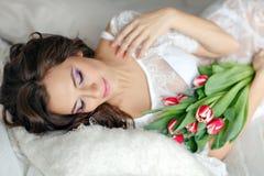 Чувственная красивая и очаровательная женщина брюнет лежа на кровати и s Стоковое Изображение