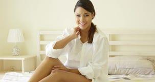 Чувственная молодая женщина протягивая на ее кровати видеоматериал