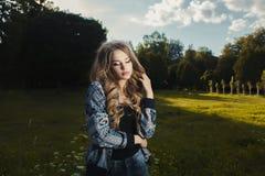 Чувственная молодая модель при длинное вьющиеся волосы представляя в парке стоковые фото