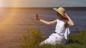 Чувственный конец вверх по портрету красивой девушки в платье лета белом на реке девушка делает selfie outdoors на camer smartpho Стоковая Фотография