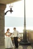 Чувственный пожененный жених и невеста пар представляя на заходе солнца на balco Стоковые Фото