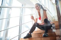 Чувственный привлекательный спортсмен женщины используя мобильный телефон Стоковое Фото