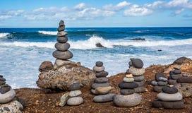 Чувствительно сбалансированные стога или кучи сделанные человеком камней с разбивать развевают стоковая фотография