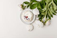 Чувствительные белые пионы и торт на белой предпосылке стоковая фотография
