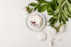 Чувствительные белые пионы и торт на белой предпосылке стоковое фото rf