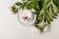Чувствительные белые пионы и торт на белой предпосылке стоковое фото