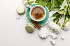 Чувствительные белые пионы с чаем, лимоном, зрелыми клубниками и печеньями на белой таблице стоковые фото