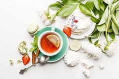 Чувствительные белые пионы с чаем, лимоном, зрелыми клубниками и печеньями на белой таблице стоковая фотография rf