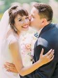 Чувствительный внешний портрет groom целуя усмехаясь невесту Стоковая Фотография RF