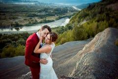 Чувствительный портрет прелестных пар новобрачных обнимая на предпосылке пышного ландшафта во время Стоковые Фотографии RF
