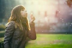 Чувствительная и хрупкая девушка, сладостная женщина надежды и природа дуя одуванчик Стоковое фото RF