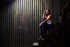 Чувствительное женское усаживание на деревянных лестницах, склонность на whil руки Стоковое Изображение