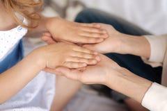 Чувствительные женские руки держа руки ребенка Стоковые Изображения