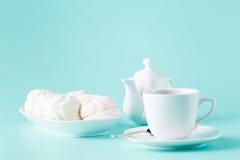Чувствительные меренги, зефиры и чашка английского чая на белизне Стоковое Фото