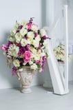 Чувствительные цветки в вазе около арфы Стоковое Изображение