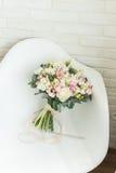 Чувствительный bridal букет на стуле стоковые изображения