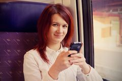 Чувствовать молодой женщины усмехаясь ослабленный и говорить к путешествовать мобильного телефона стоковая фотография